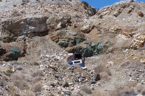 The copper in the material causes the oxidation of the material in the rock which in turns makes the rocks blue.